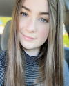 Kaitlyn Kretsinger Dunham is a White woman with long brown hair wearing a black and white striped turtleneck shirt.