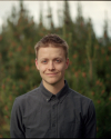Portrait of Jacob Wilson with shallow depth of field with greenery in the background.
