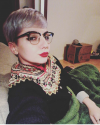 a person with bleached, short hair stares sideways at the camera. They are wearing a colorful sweater, red lipstick, cat's eyeliner, and black and gold framed glasses