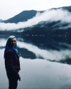 Woman with blue hair in a red leather jacket standing in front of Lake Crescent