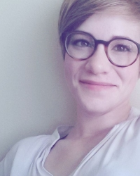 A headshot of a woman with short hair and glasses.