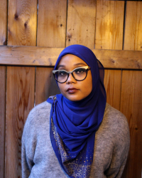 Sumayyah standing in front of a wood panel background in a blue hijab and grey sweater.