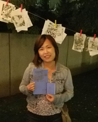 On the background of a line of print artworks, a woman with short hair is holding a couple of booklets.