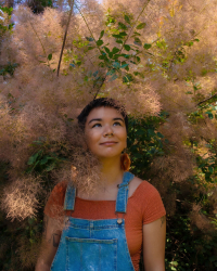 Ally Ang, a short haired Asian person, stands among trees, wearing overalls and an orange shirt.