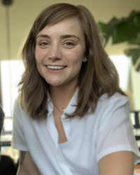 Femme queer person with light brown, wavy hair just past the shoulders and side bangs. There is sunlight in the background and they are wearing a white button down shirt and are smiling at the camera with an overbite, thick brown eyebrows, & hazel eyes ey